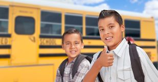 Two Young Hispanic Brothers Walking Near School Bus stock photography