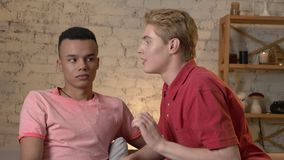 Two young homosexual boys are sitting on the couch, american guy with short hair tells the secrete to his partner. African guy agrees 60 fps 4k stock footage