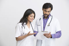 Two young Indian attractive doctors discussion with document. Stock Image