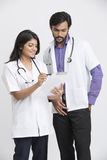 Two young Indian attractive doctors examining the document. Stock Image