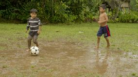 Two young indigenous boys are playing football on a muddy pitch