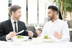 Businessmen communicating. Two young intercultural businessmen sitting by served table during business lunch and communicating Stock Photography