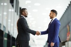 Handshake after deal. Two young intercultural delegates in suits shaking hands while greeting one another before meeting or summit Stock Image
