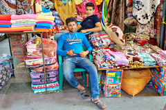 Two young Iranian traders trade textiles in the Grand Bazaar. Royalty Free Stock Photos