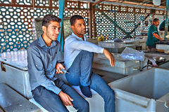 Two young Iranians are resting at entrance to  fish market. Royalty Free Stock Photography