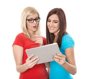 Two young isolated woman looking at tablet-pc: concept for datin Stock Photography