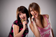 Two Young karaoke girls Royalty Free Stock Images