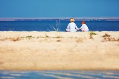 Two young kids, brothers sitting on sandy beach in the morning on the lake coast Stock Image