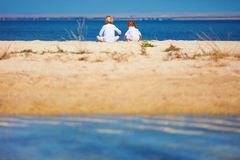 Two young kids, brothers sitting on sandy beach in the morning near the lake Royalty Free Stock Photos