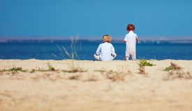 Two young kids, brothers sitting on sandy beach in the morning near the lake Royalty Free Stock Photo
