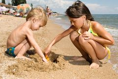 Two young kids digging sand at the beach. Small brother and sister spending their vacation at the summer resort Stock Image