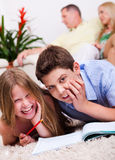 Two young kids lying with a book in living room Stock Photo