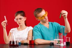 Two laboratory assistant are studying some kind of liquid in flasks. On a red background. Two young laboratory assistant girl and boy, in uniform and glasses Royalty Free Stock Photos