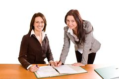 Two young ladies at desk royalty free stock photography