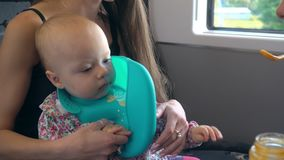 Two Young Ladies Feeding a Baby on the Train stock image