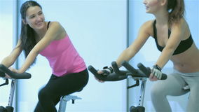 Two young ladies girl pedaling on the simulator stock footage