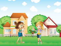 Two young ladies playing in the ground in front of the houses Stock Photo