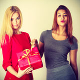 Two young ladies with red gift. Stock Photos