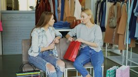 Two young ladies sitting in clothes department in mall and talking after shopping. Colourful women`s garments and. Two young attractive ladies sitting in clothes stock footage