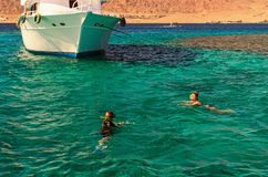 Two young ladies are snorkeling in clean water over reef near the moored yacht. Travel and tourism concept. Red Sea, Dahab, Egypt stock image