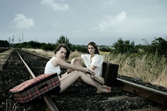 Two young ladies with suitcases. Two young ladies sit on the rails with old fashioned suitcases Royalty Free Stock Image