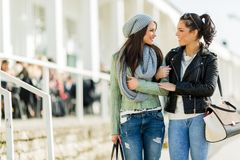 Two young ladies walking and shopping happily while looking at e Royalty Free Stock Photography