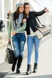 Two young ladies walking and shopping happily pointing in a dire Stock Images