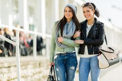 Two young ladies walking and shopping happily on a sunny day Stock Photos