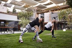 Two young ladies, 20-29 years old, doing some kind of exercise in jump boots,. In a backyard of a fancy house stock images