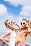 Two young lady in summer apparel pose for the camera Royalty Free Stock Photography
