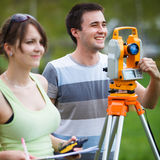 Two young land surveyors Stock Photos
