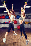 Two young laughing fitness women jumping in gym Royalty Free Stock Images