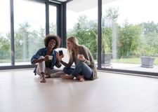 Multiethnic women sit on the floor and drinking coffee Royalty Free Stock Images