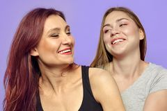 Two young laughing women, one caucasian blonde, another one latin. Beautiful diversity, fun and tight relationship, strong emotion royalty free stock photos