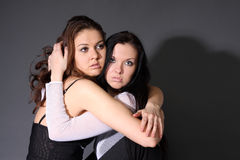 Two young lesbian girl friend. On gray background Stock Photo
