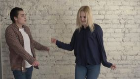 Two young lesbian girls dancing against a bricky white wall background, happy couple, lgbt family concept 60 fps. 4k stock footage