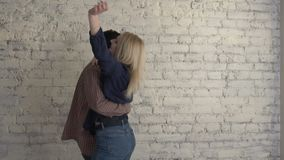 Two young lesbian girls dancing against a bricky white wall, happy couple, lgbt family concept, lovers 60 fps. 4k stock video