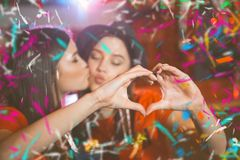 Two young lesbian girls kiss and make a heart with their hands at a club party.  stock photography