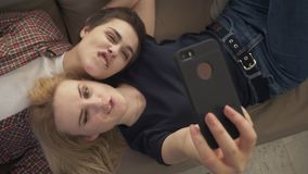 Two young lesbian girls lie on the couch, do selfie on a smartphone, lovers, lgbt, young couple, teenagers top shot 60. Two young lesbian girls lie on the couch stock footage