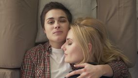 Two young lesbian girls lie on the couch, hug, cuddle, sleep, girl with short hair looks at the camera, lgbt family. Concept, happy, top shot, relaxation 60 fps stock video