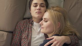 Two young lesbian girls lie on the couch, hug, cuddle, sleep, girl with short hair looks at the camera, lgbt family. Concept, top shot 60 fps 4k stock video footage