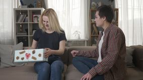 Two young lesbian girls are sitting on the couch, a girl with blond hair is pleased with the gift, hugs 60 fps. 4k stock video