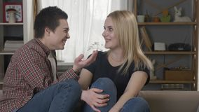Two young lesbian girls are sitting on the couch, a girl with blond hair tells the secrquet to her partner, a girl with. Short hair laughs 60 fps 4k stock footage
