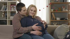 Two young lesbian girls sitting on the couch, pregnant blonde caresses the belly, waiting for the baby`s appearance. Coziness, love, happiness. 60 fps 4k stock video