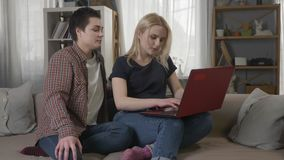 Two young lesbian girls are sitting on the couch, using a computer, scrolling the internet, shopping online 60 fps. 4k stock footage