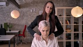 Two young lesbians in office, beautiful business woman massaging other woman, relaxing and pleasant.  stock video footage