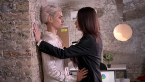 Two young lesbians in office, confident woman pushing other woman to wall, sexy and attractive.  stock video footage
