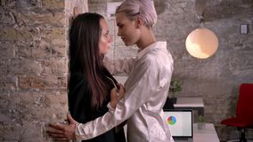 Two young lesbians in office, confident woman putting other woman to wall, sexy and attractive.  stock footage
