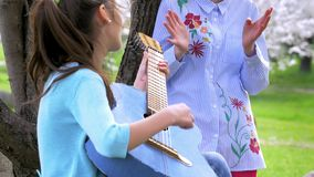 Two Young little girl relaxing with guitar in nature and enjoying sunny day. one juvenile girl plays guitar for his girlfriend. be. Two Young little girl stock video footage