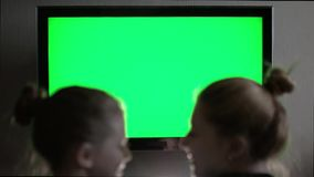 Two young long-haired blond looking at green screen TV in evening home interior. stock video